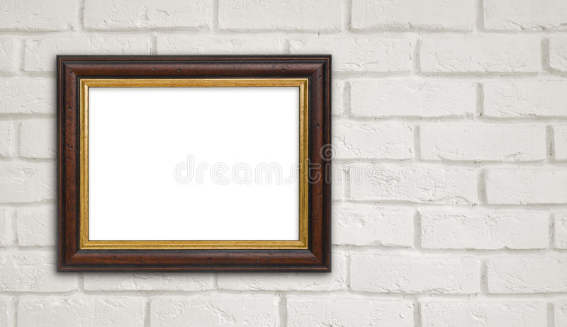 Brown vintage picture frame on white brick wall with copyspace stock image