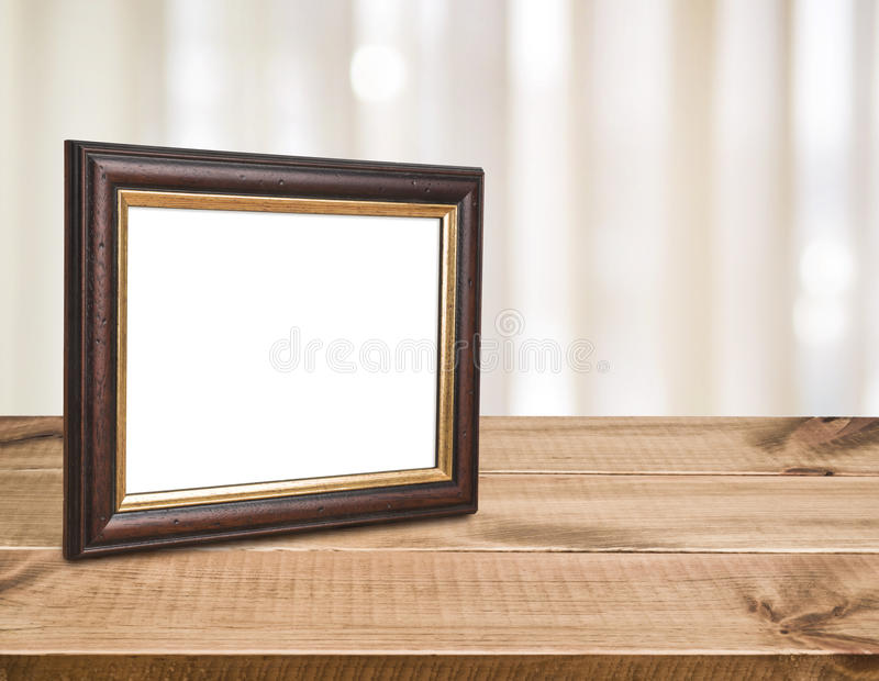 Brown vintage picture frame on wood over abstract curtain background.  stock photo