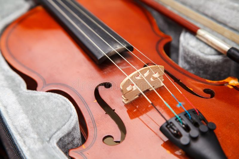 Brown vintage violin with bow lying in a case royalty free stock image