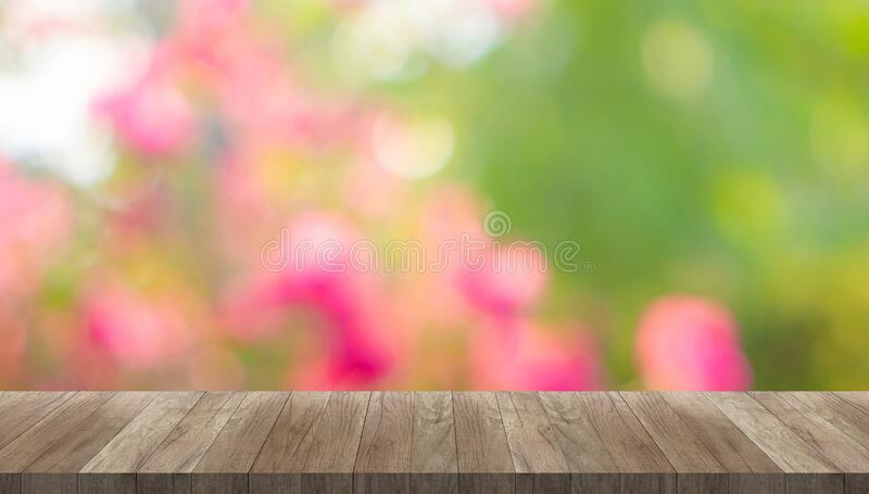 Brown vintage wooden table desk and copy space on bokeh image abstract blurred backgrounds from pink flower blossom and green. Leaves stock images