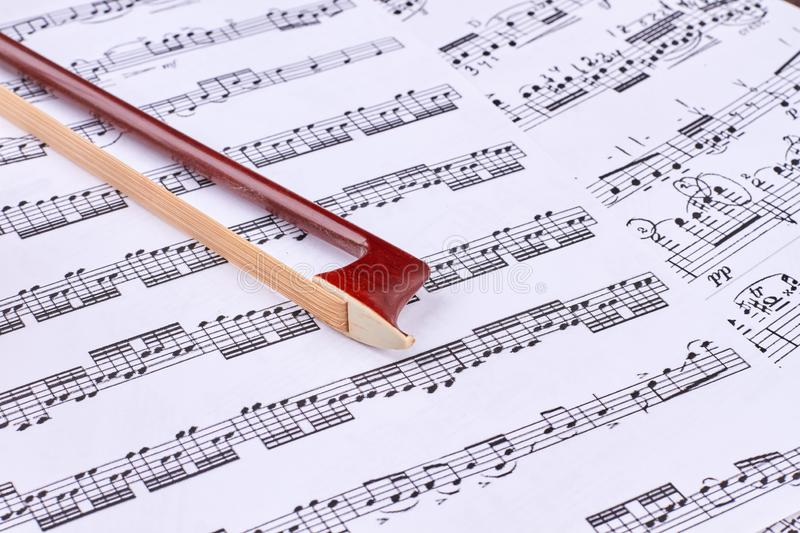 Brown violin bow on musical notes sheets. stock image