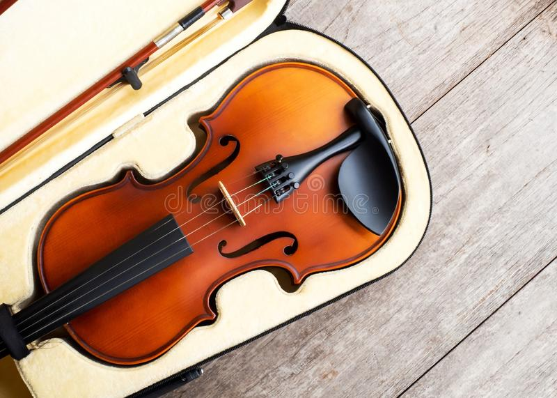 Brown violin in case over wooden background. Art and music background. stock image