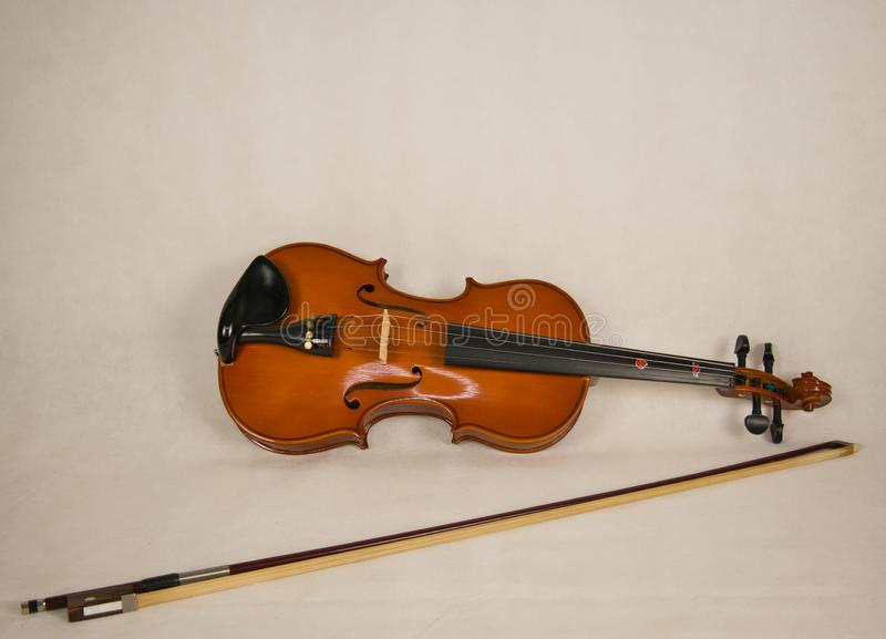 Brown violin with four strings and a violin bow royalty free stock photography