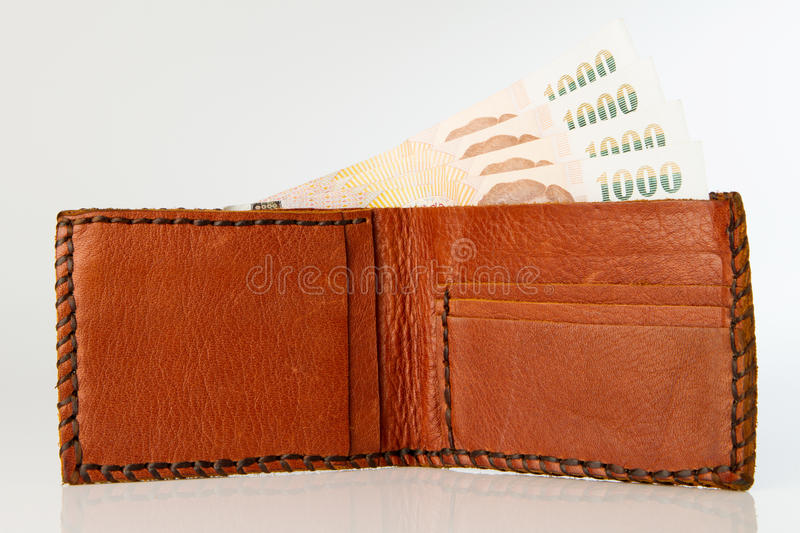 Brown wallet. With Thai Baht Paper Currency on the white background royalty free stock photo