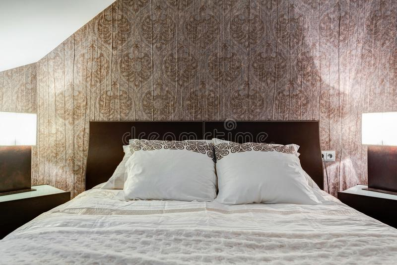 Brown wallpaper in elegant bedroom. Comfortable bed and brown wallpaper in elegant bedroom stock photography