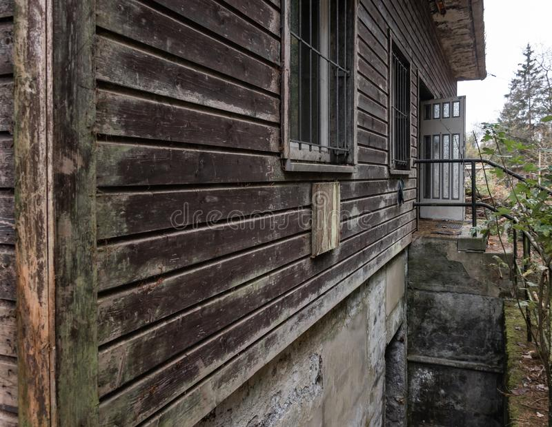 Brown weathered facade of an old abandoned wooden house in the mountains, close-up view from the house corner. stock photo