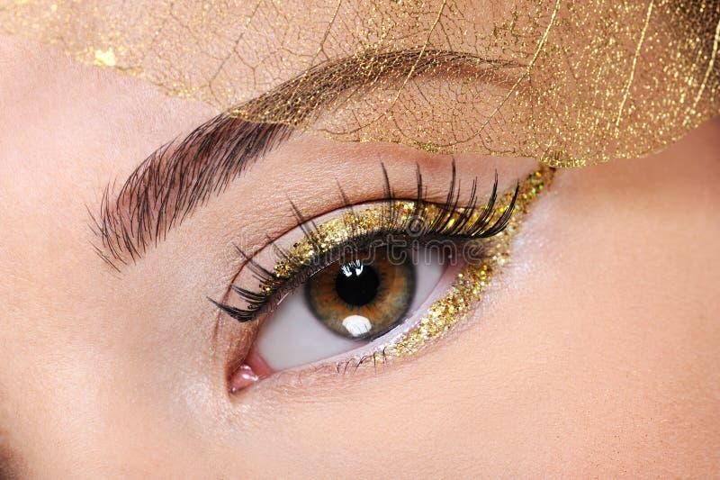 Brown-weibliches Auge mit einer goldenen Verfassung des Zaubers lizenzfreies stockfoto
