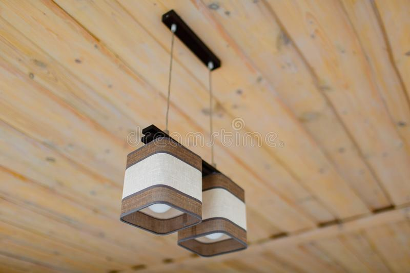 Brown and white chandelier hanging on wooden ceiling stock photography