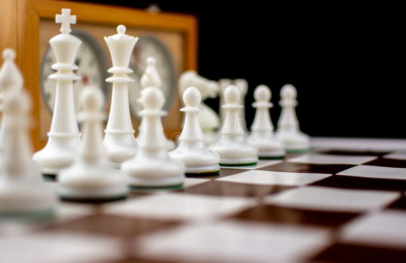 Brown and white chess board with chess pieces stock photography