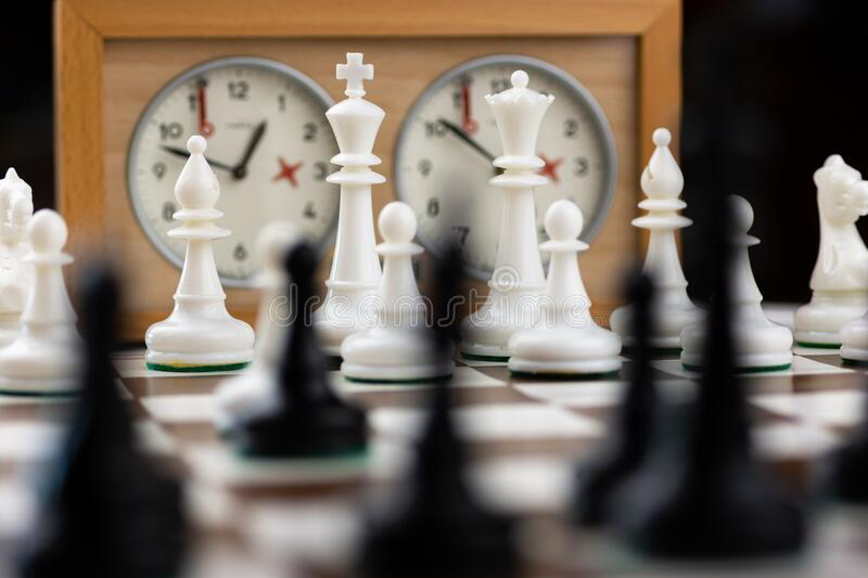 Brown and white chess board with chess pieces stock images