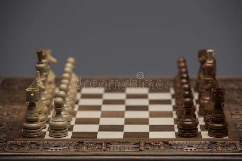 Brown and white figures on chess desk stock photography