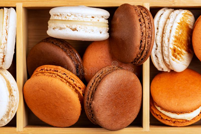 Brown and white french macarons or macaroons, stacked in a three compartments box. Brown and white french macarons or macaroons, chocolate, coffee, toffee royalty free stock image