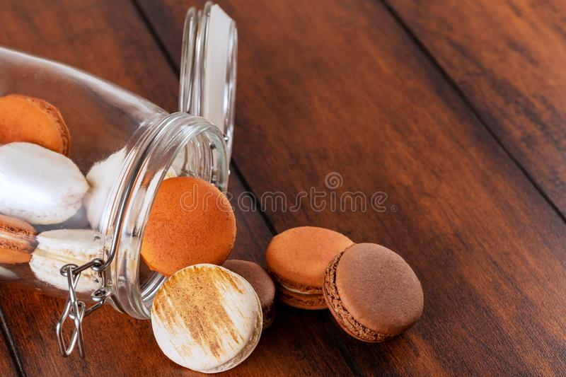 Brown and white french macarons or macaroons, falling out of a glass jar over a vintage wood background with copyspace royalty free stock photography