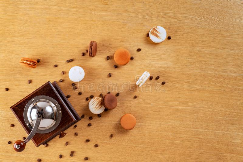 Brown and white french macarons or macaroons spread over an oak wood background with a coffee mill on the side and coffee beans sp royalty free stock photography
