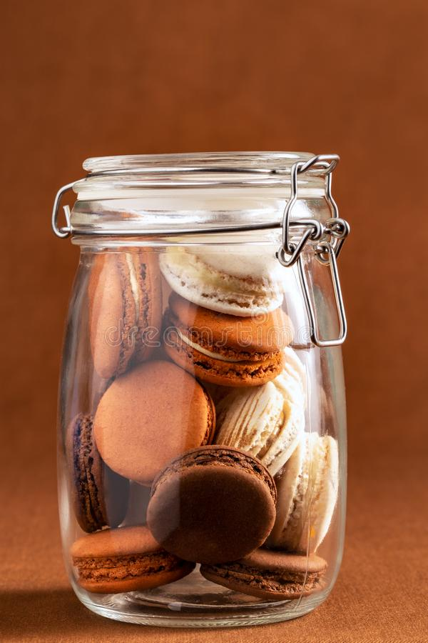 Brown and white french macarons or macaroons, stacked inside a vintage glass jar over a chocolate brown background. stock images