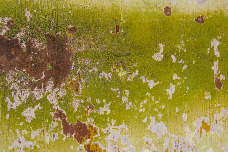Brown, white, green, yellow, old shabby wall with rust and paint stains. rough surface texture royalty free stock photos