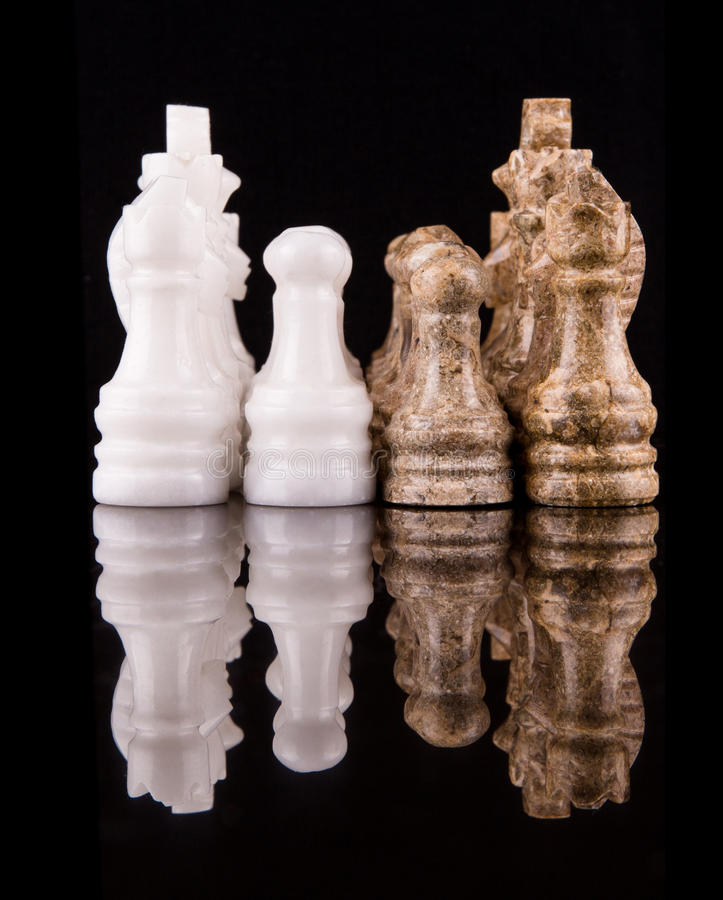 Brown And White Stone Made Chess Set I. Brown and white pieces of stone made chess set on black background stock photo