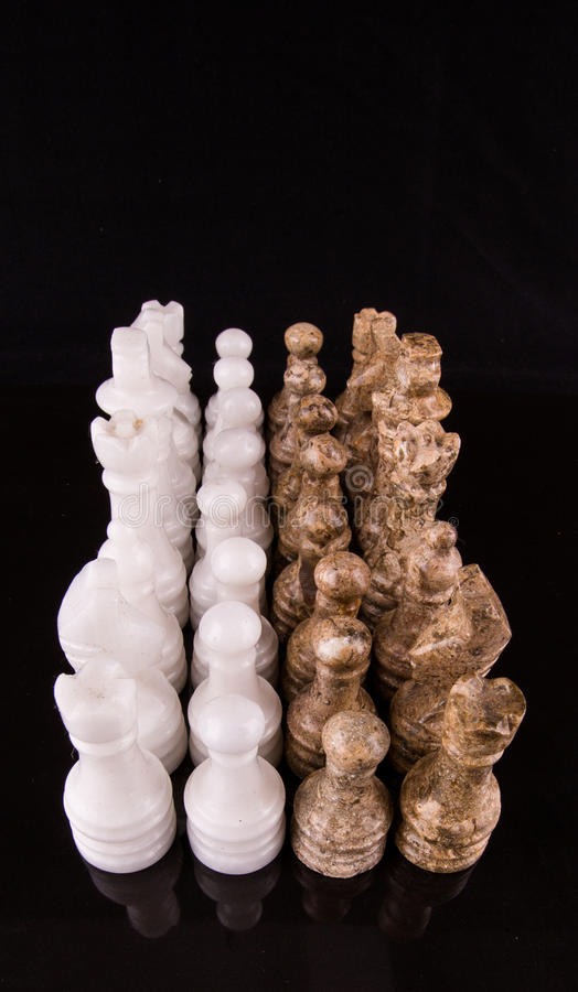 Brown And White Stone Made Chess Set IV. Brown and white pieces of stone made chess set on black background royalty free stock images