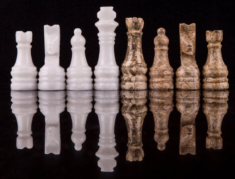 Brown And White Stone Made Chess Set V. Brown and white pieces of stone made chess set on black background stock image