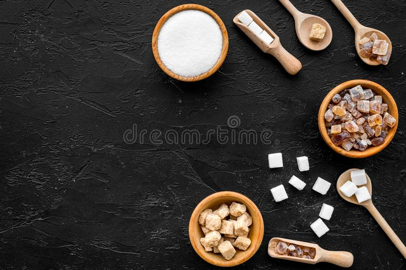 Brown and white sugar in bowls, scoop and spoon. Cane, refind, granulated, cubes, candy. Black background top view copy royalty free stock images