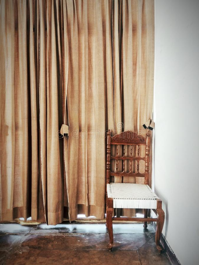 Brown And White Wooden Chair Beside A Brown Window Curtain stock image
