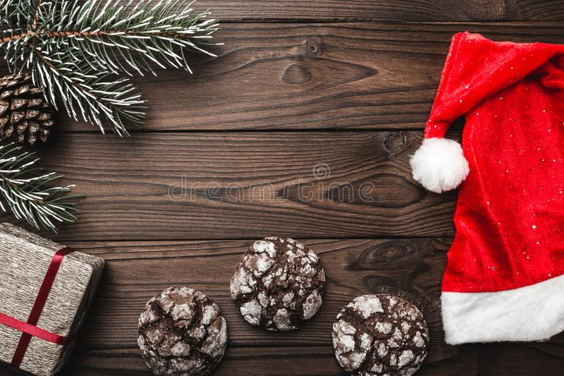 Brown wood background. greeting card. Santa`s Cap. Fir tree, decorative cone. Sweets. Message space for Christmas and New Year. Gifts for xmas. Xmas and Happy stock photo