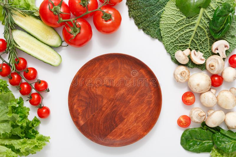 Brown wood cutting board, border of fresh vegetables on white background with copy space. Brown wood cutting board, border of fresh organic vegetables, fruits stock image