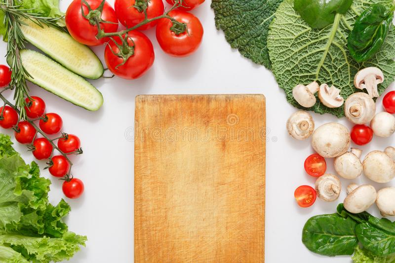 Brown wood cutting board, border of fresh vegetables on white background with copy space. Brown wood cutting board, border of fresh organic vegetables, fruits stock images
