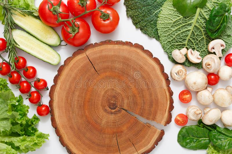 Brown wood cutting board, border of fresh vegetables on white background with copy space. Brown wood cutting board, border of fresh organic vegetables, fruits royalty free stock photography