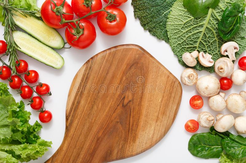 Brown wood cutting board, border of fresh vegetables on white background with copy space. Brown wood cutting board, border of fresh organic vegetables, fruits royalty free stock photos