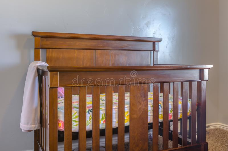 Brown wooden baby crib with blanket. In clean home in Utah Valley stock photography