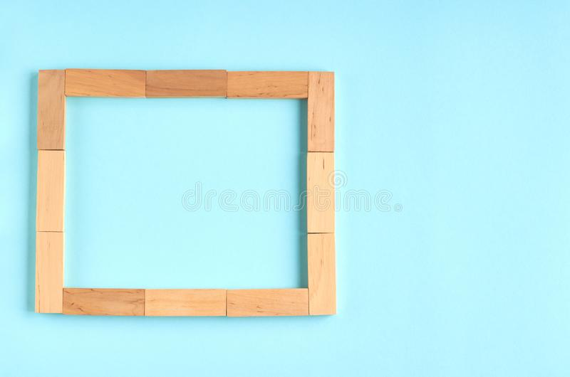 Brown wooden blocks frame shape idea on blue background composition. Flat lay and top view photo, border, bricks, layout, above, bright, card, concept, copy stock images