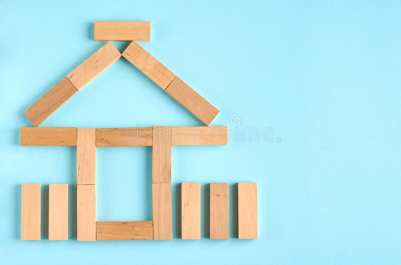 Brown wooden blocks house shape idea on blue background composition. Flat lay and top view photo, home, bricks, layout, above, bright, card, concept, copy stock images