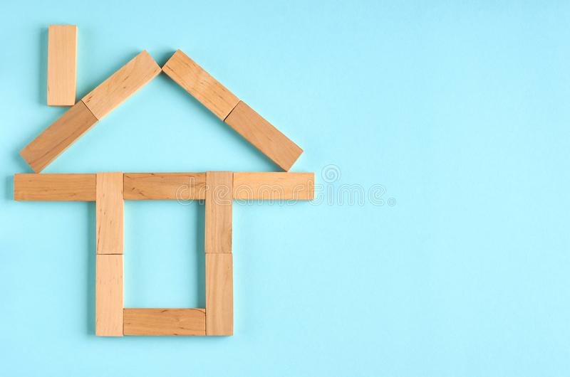 Brown wooden blocks house shape idea on blue background composition. Flat lay and top view photo, home, bricks, layout, above, bright, card, concept, copy stock photography