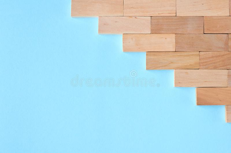 Brown wooden blocks idea on blue background composition. Flat lay and top view photo, border, wall, bricks, layout, above, bright, card, concept, copy, space royalty free stock photography
