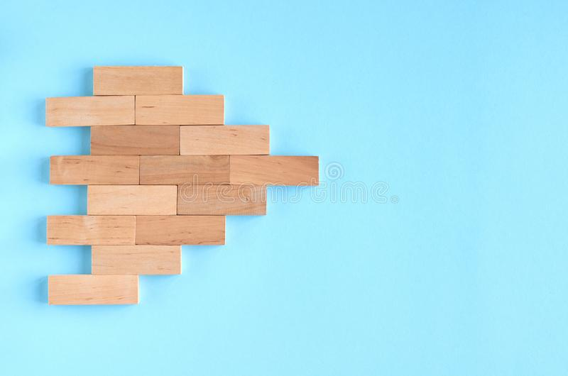 Brown wooden blocks ship or arrow idea on blue background composition. Flat lay and top view photo, bricks, layout, above, bright, card, concept, copy, space royalty free stock image