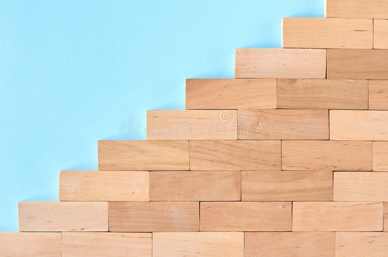 Brown wooden blocks stairs shape idea on blue background composition. Flat lay and top view photo, border, wall, bricks, layout, above, bright, card, concept stock photo