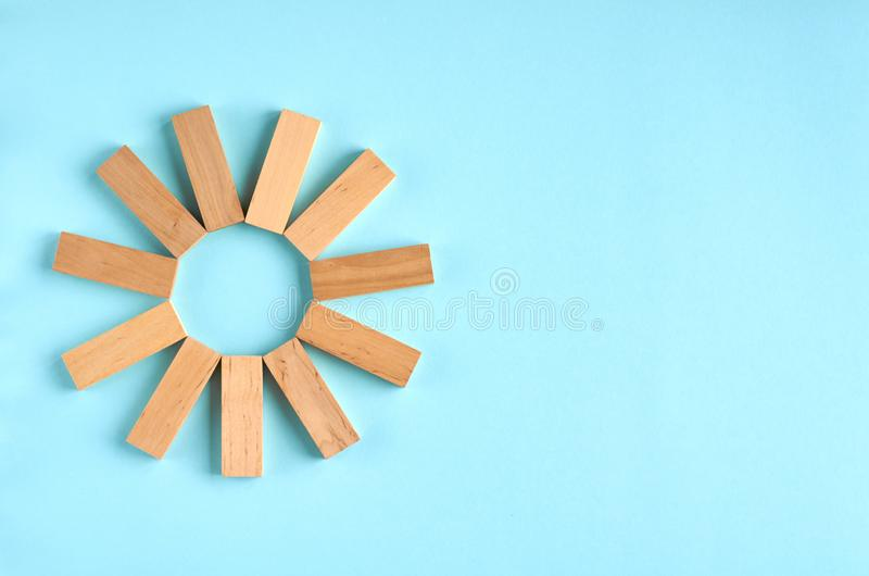 Brown wooden blocks sun or star shape idea on blue background composition. Flat lay and top view photo, bricks, layout, above, bright, card, concept, copy stock images