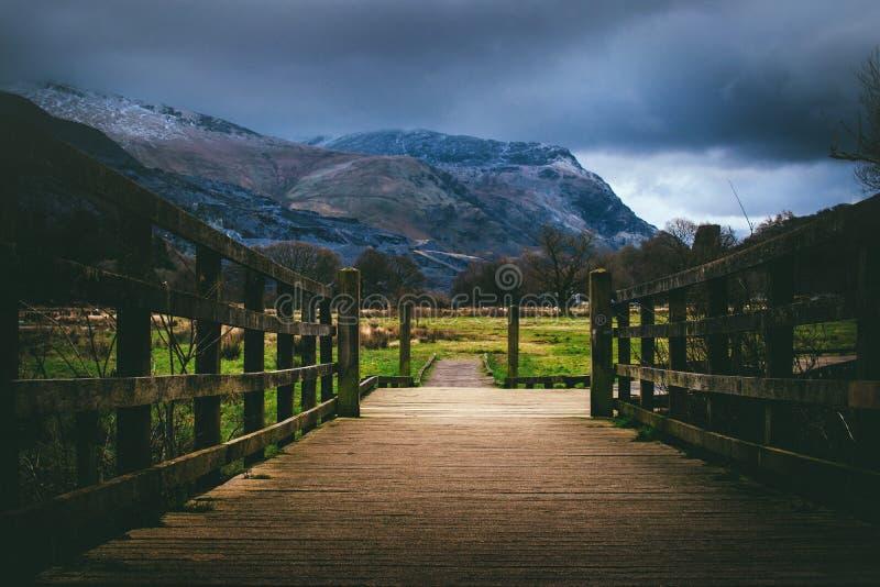 Brown Wooden Bridge Near Mountain at Daytime stock photo