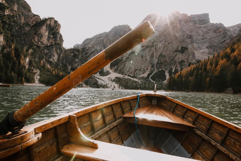Brown Wooden Canoe on Body of Water Near Mountain royalty free stock photo