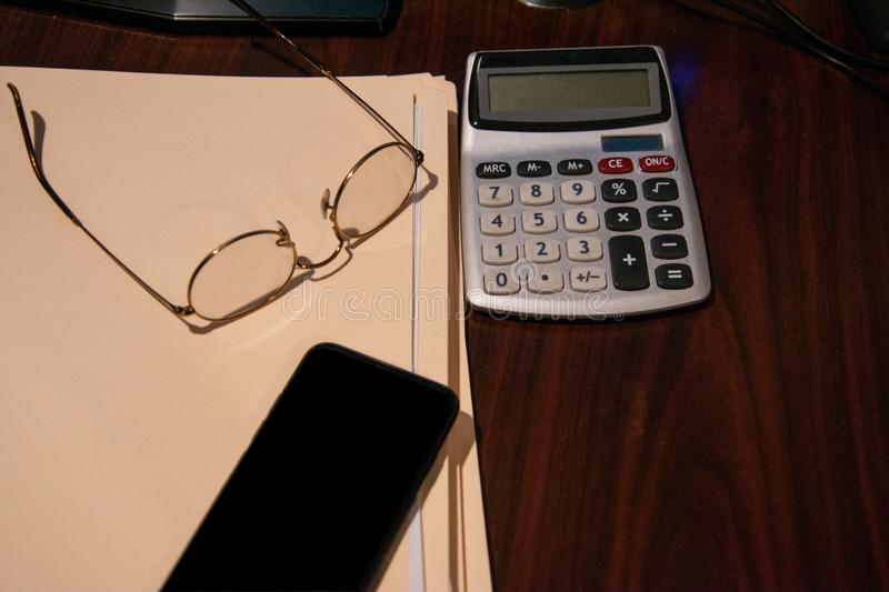 Brown wooden desk with several closed file folders a calculator and glasses turned upside down and a cell phone. stock photography