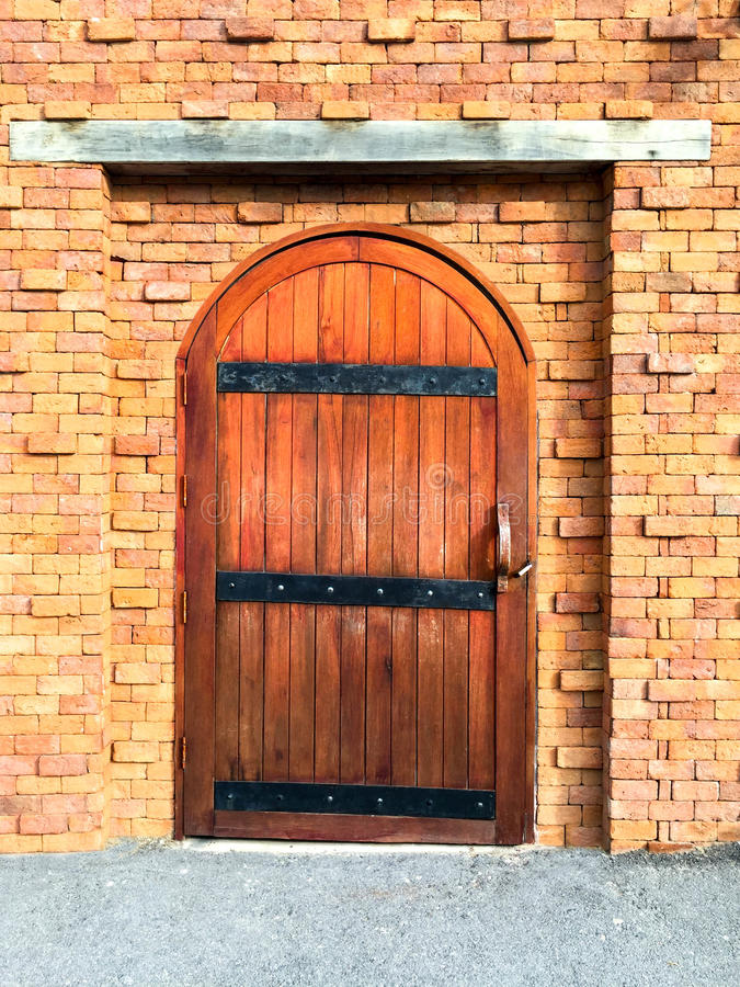 Brown wooden door with red brick wall stock images