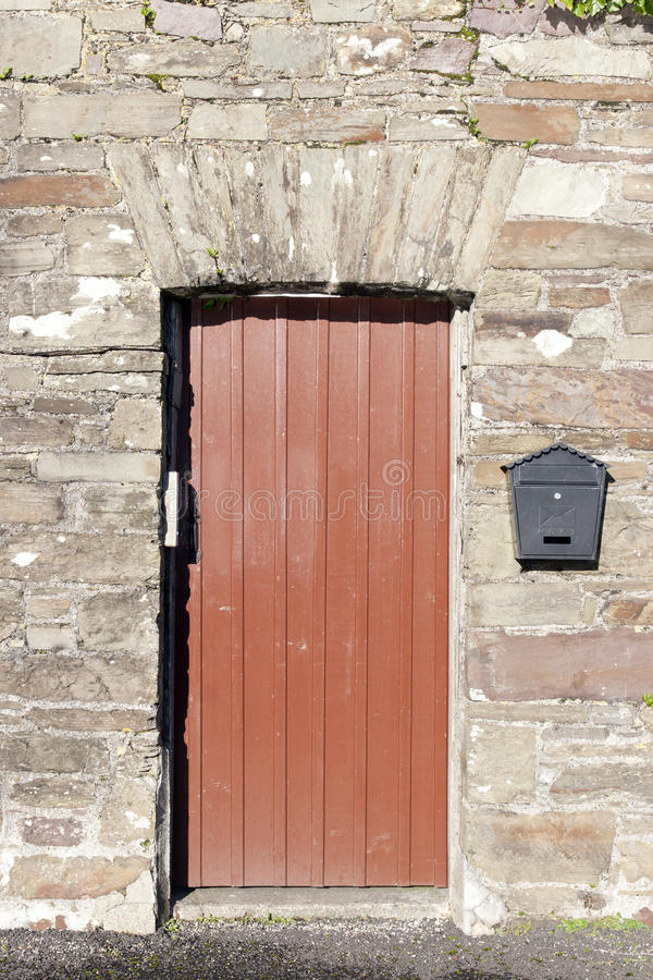 Brown wooden doorway and a post box. On old stone wall royalty free stock photography
