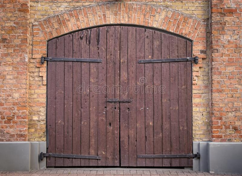 Brown wooden double doors with a red brick arch. royalty free stock photos