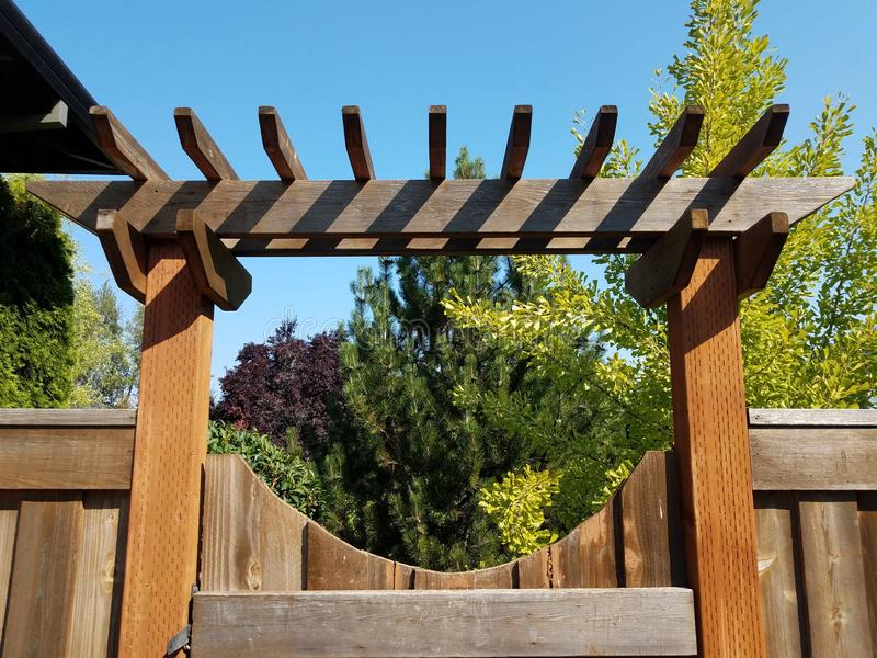 Brown wooden fence and gate with lattice. And trees and sky stock photography