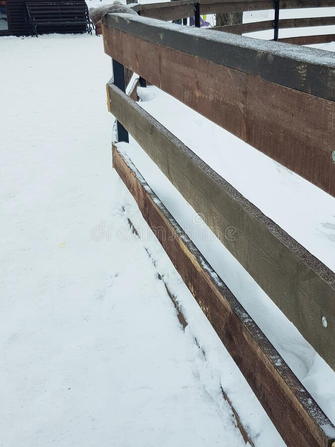 Brown wooden fence from horizontal boards on a background of snow in winter, rustic style, copy space stock images