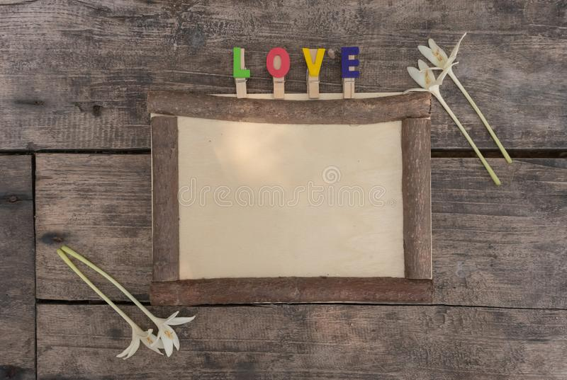 Brown wooden frame with LOVE letters and Millingonia on the rough wooden table. Background of the rock wall. Sun light shines on t stock images