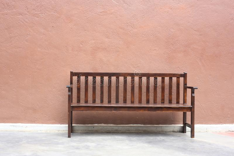 Brown wooden garden chair with brown cement wall. Brown wooden garden chair with brown cement backgound stock photo