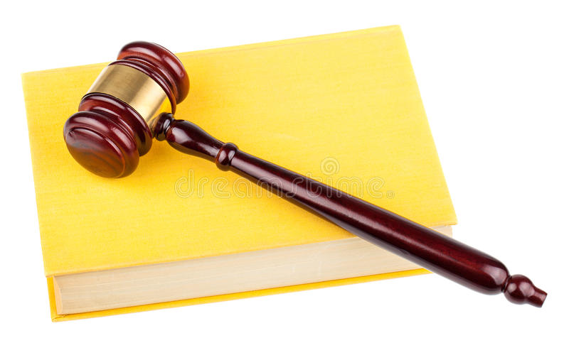 Wooden gavel on yellow book. Brown wooden gavel and yellow book isolated on white background royalty free stock photo