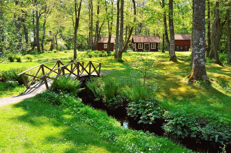 Brown Wooden House Near the Creek With a Bridge royalty free stock photo
